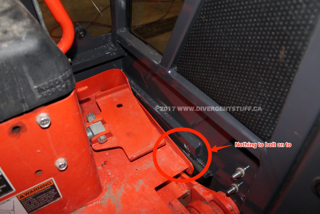 Inside the Backhoe Cab showing the cab mounting bolt location.  It appears that Kubota changed the backhoe skirt and added a notch to make it easier to fit boots onto the backhoe thumb actuator.  Laurin's cab does not reflect this change.