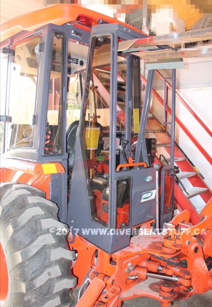 Using the fork lift to install the backhoe cab.